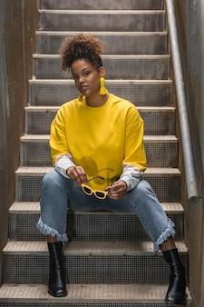 Модная черная женщина в желтой одежде сидит на лестнице