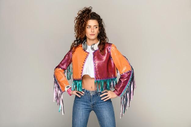 Модная богемная молодая женщина в разноцветной куртке с бахромой с кисточками стоит подбоченясь с руками за бедра на светло-сером студийном фоне