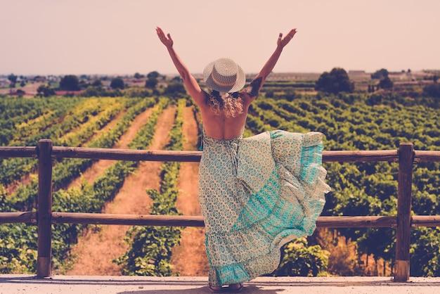 美しいブドウ園の風景の前で自由な気分のために腕を開く女性のトレンディな自由奔放に生きるシックなスタイル-アウトドアと旅行の人々のライフスタイルの概念-ファッション女性のドレスを後ろから見た