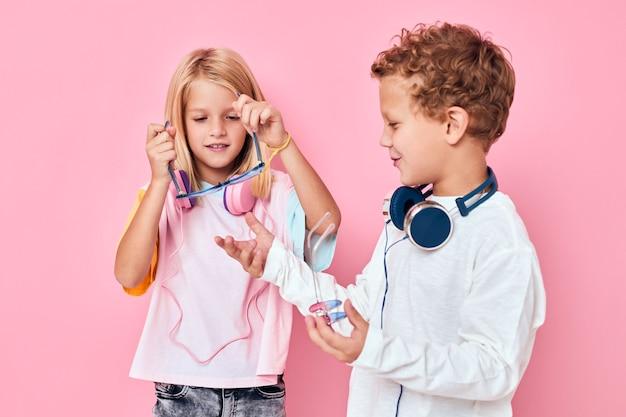 Модный мальчик и девочка в наушниках позирует в розовом цвете