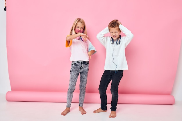 Trendy boy and girl entertainment headphones playing childhood lifestyle concept