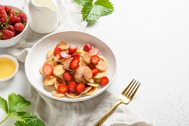 Модный завтрак с мини-блинами и клубникой на белой поверхности