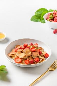 Модный завтрак с мини-блинами и клубникой на белой поверхности Premium Фотографии