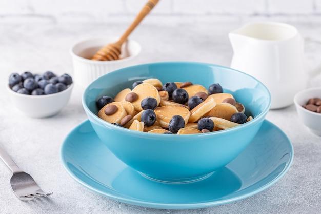 미니 팬케이크, 블루 베리, 초콜릿 칩, 선택적 포커스가있는 트렌디 한 아침 식사.