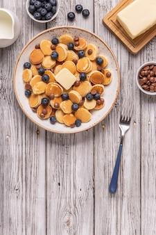 ミニパンケーキ、ブルーベリー、チョコレートチップ、トップビューのトレンディな朝食。