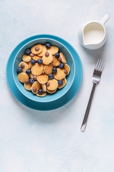 미니 팬케이크, 블루 베리, 초콜릿 칩으로 구성된 트렌디 한 아침 식사