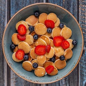 ミニパンケーキ、ブルーベリー、イチゴ、トップビューのトレンディな朝食。
