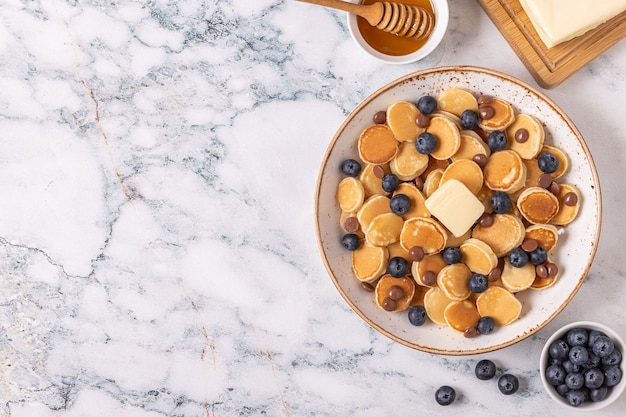Trendy breakfast with mini pancakes, blueberries and chocolate chips, top view.