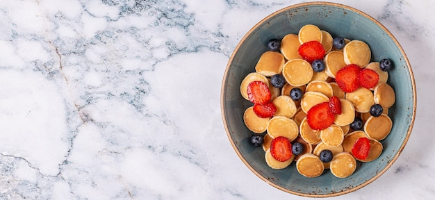 Trendy breakfast with mini pancakes, blueberries and strawberries, top view.