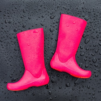 Trendy bright pink rubber boots on black wet surface covered with raindrops