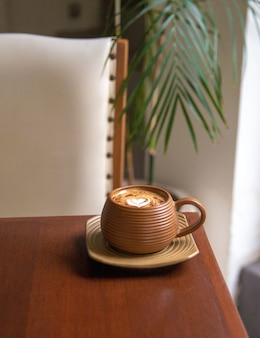Trendy brown cup of hot cappuccino on wooden table background