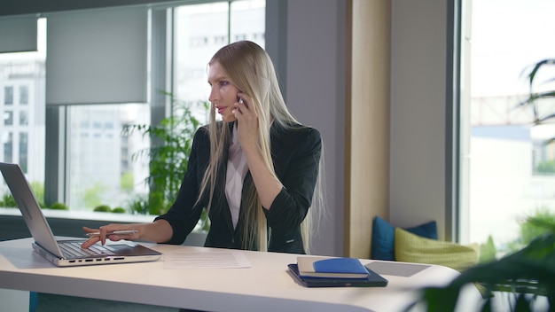 Trendy business woman watching laptop and speaking on phone.