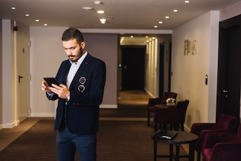 Trendy businessman in hall with gadget