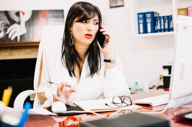 Trendy businesswoman in office talking on phone