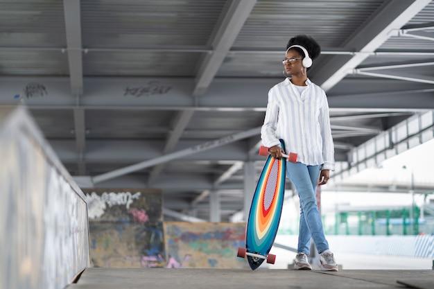 헤드폰을 끼고 있는 트렌디한 캐주얼 흑인 여성은 스케이트파크나 트렌디한 도시 공간 배경에서 롱보드를 들고 있습니다.