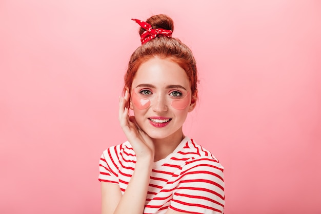 미소로 카메라를보고 눈 패치 유행 백인 여자. 분홍색 배경에 고립 된 스트라이프 티셔츠에 생강 여자의 스튜디오 샷.