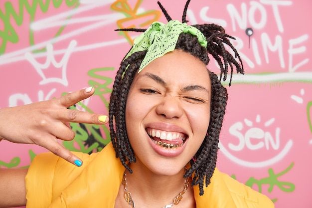 Trendy cheerful hipster girl makes yo gesture shows golden teeth and tongue winks eye enjoys cool modern music stands near graffiti wall enjoys her freedom