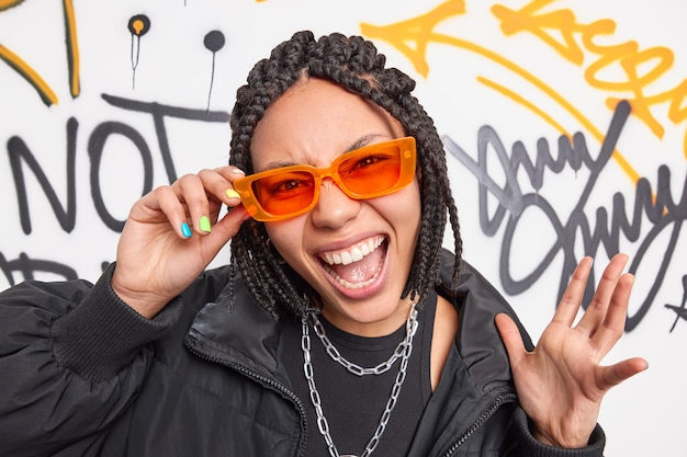 Trendy cheerful hipster girl wears orange sunglasses black jacket raises hand exclaims loudly has cheeky expression has own fashion style poses against creative painted street wall