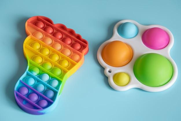 Модные детские игрушки-антистресс и простая ямочка крупным планом на синем фоне.