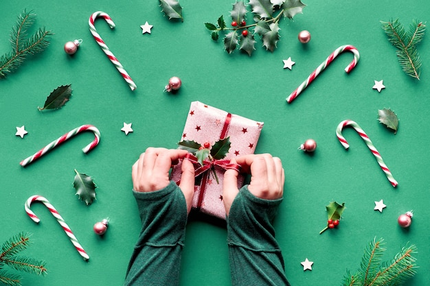 Trendy christmas flat lay  with candy canes, holly and fir twigs, wooden stars and glass trinkets. female hands tie up ribbon on gift box wrapped in pink wrapping paper.