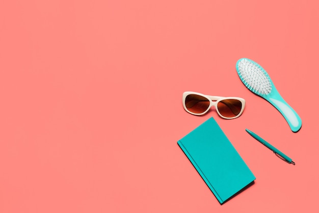 Trendy colorful flat lay composition. coral colored desk with turquoise diary, hair comb, white glasses and pen.