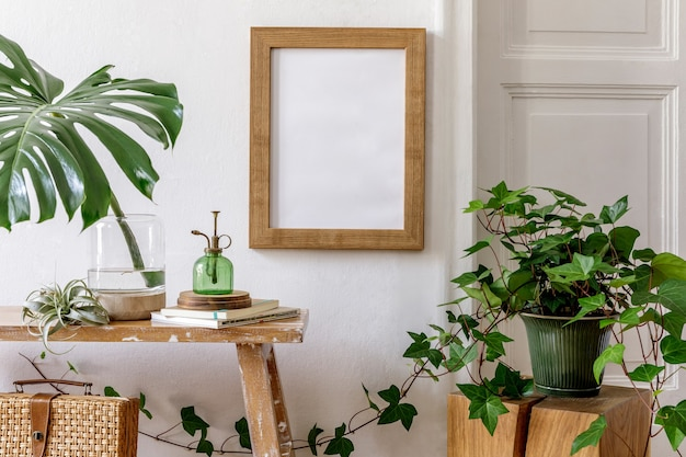 Trendy composition of home garden interior with frame, wooden bench, plants in design pots, tropical leaf in vase, decoration, personal accessories in stylish home decor.