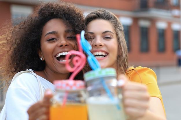 Модные крутые хипстерские девушки, друзья пьют коктейль на фоне городского города.