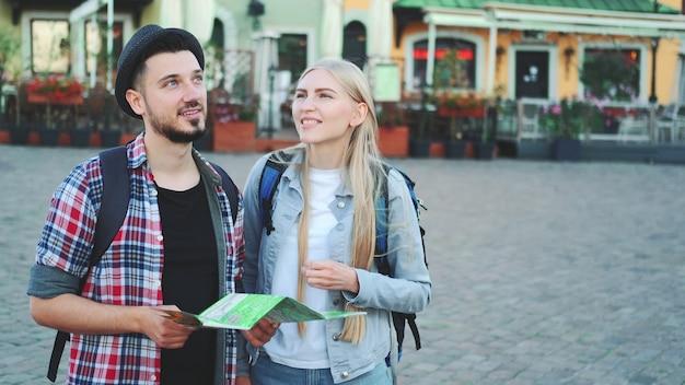 Модная парочка туристов, которые находят нужное место на карте и любуются окрестностями. они стоят на городской площади.