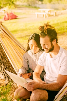 Trendy couple relaxing together in hammock outdoors
