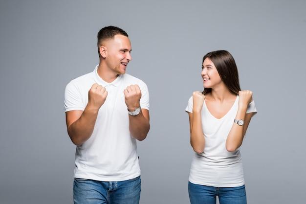 Coppia alla moda in piedi su sfondo grigio divertendosi dalla vittoria di una buona notizia