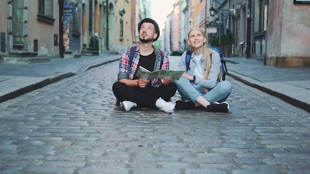 Trendy couple of tourists using map, sitting on pavement and admiring historical surroundings