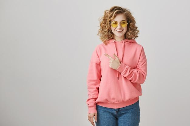 왼쪽을 가리키는 방법을 보여주는 선글라스에 유행 귀여운 곱슬 머리 소녀