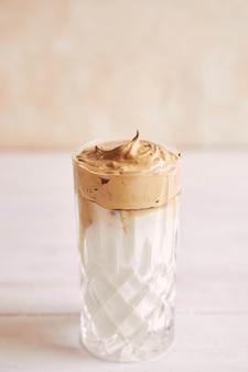 白い木のテーブルの上に牛乳とトレンディなおいしい新鮮なダルゴナコーヒー