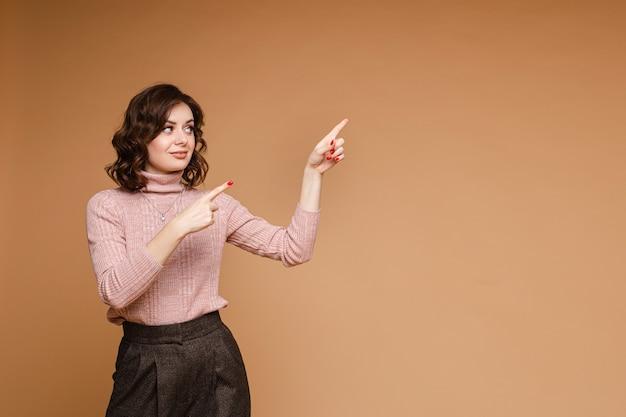 거북이 목이 있는 옅은 분홍색 스웨터에 중간 길이의 어두운 물결 모양의 머리를 한 세련된 옷을 입은 여성