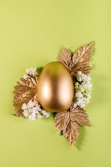 Модный пасхальный фон с золотым пасхальным яйцом и золотыми листьями на светло-зеленом цветном фоне с пустым пространством для текста Premium Фотографии