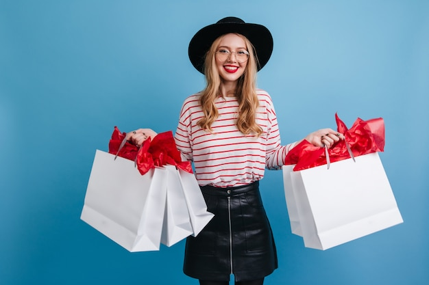 ショッピングバッグを保持している帽子のトレンディなヨーロッパの女の子。青い背景の上に立っている魅力的な金髪の女性モデル。