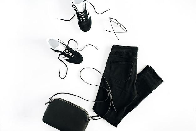 Модная женская одежда и аксессуары в черном стиле выглядят на белой поверхности