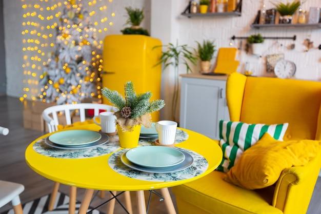 밝은 노란색 가구와 새해 조명으로 장식 된 스튜디오 아파트의 스칸디나비아 스타일의 트렌디 한 패션 럭셔리 인테리어 디자인