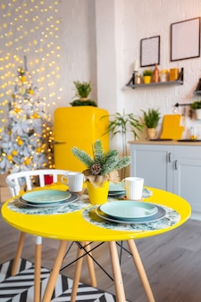 Trendy fashion luxury interior design in scandinavian style of studio apartment with bright yellow furniture and decorated with new year lights