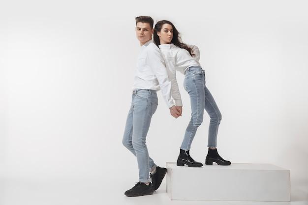 白い壁に分離されたトレンディなファッショナブルなカップル