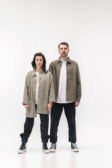 Trendy fashionable couple isolated on white studio wall.