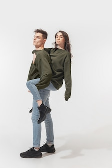Trendy fashionable couple isolated on white wall