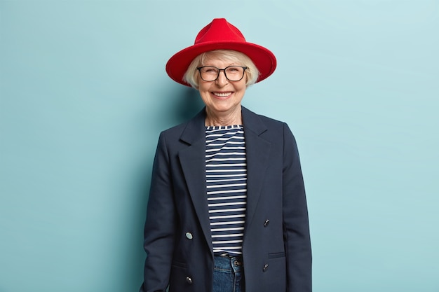 Trendy fashionable elderly woman smiles happily, shows white teeth, has wrinkled skin, dressed in stylish formal clothes, being in good mood, ready for work, enjoys nice day, isolated on blue wall