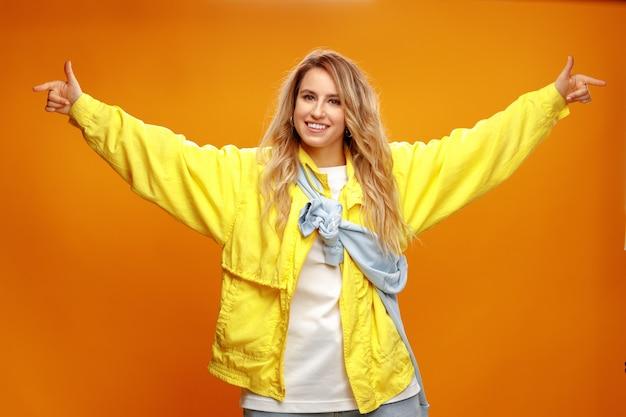 Модная модная танцовщица позирует на желтом фоне