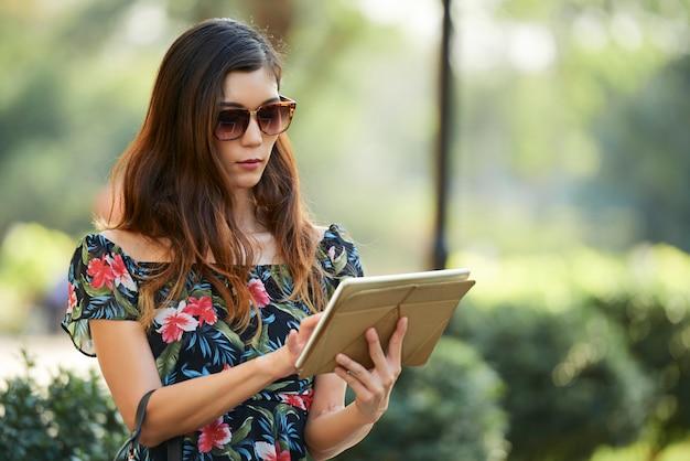 Trendy female using tablet near park