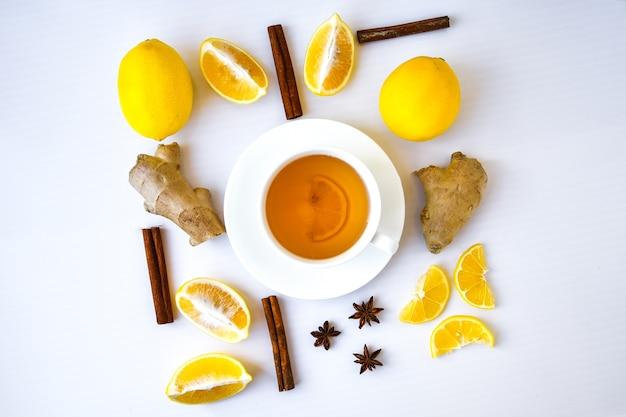 흰색 배경에 소박한 스타일로 감귤류 레몬 계피와 함께 비타민 천연 음료를 강화하는 트렌디한 플랫 레이 진저 핫 면역. 카모마일 차. 건강한 개념