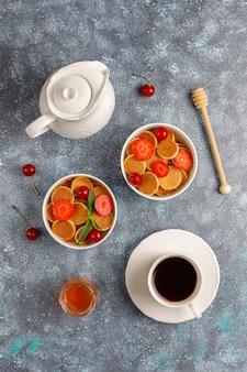 Cibo alla moda - cereali mini pancake. mucchio di frittelle di cereali con frutti di bosco e noci.