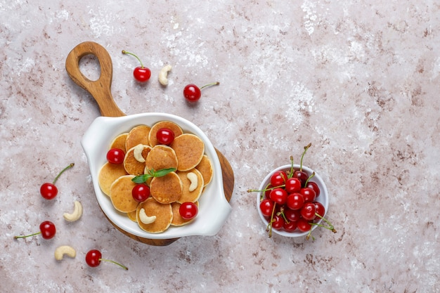 Trendy food - mini pancake cereal. heap of cereal pancakes with berries and nuts.