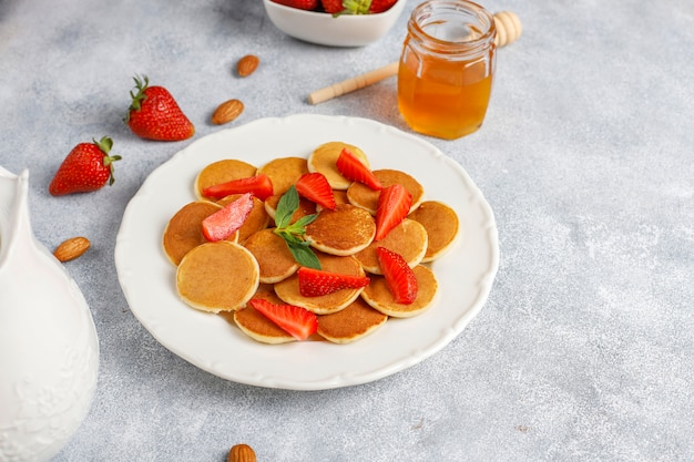 トレンディな食品-ミニパンケーキシリアル。ベリーとナッツのシリアルパンケーキのヒープ。