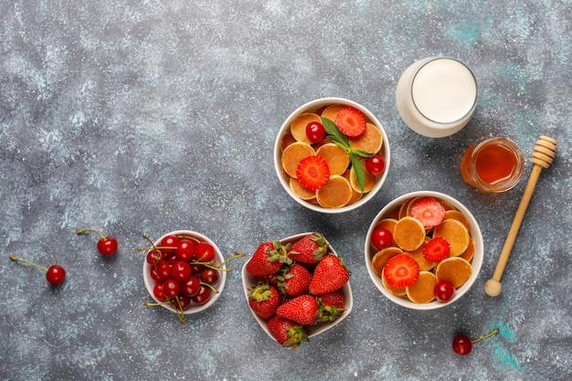 최신 유행 음식-미니 팬케이크 시리얼. 딸기와 견과류와 시리얼 팬케이크의 힙입니다.